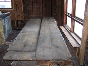 Wide board flooring before restoration in timber frame barn home
